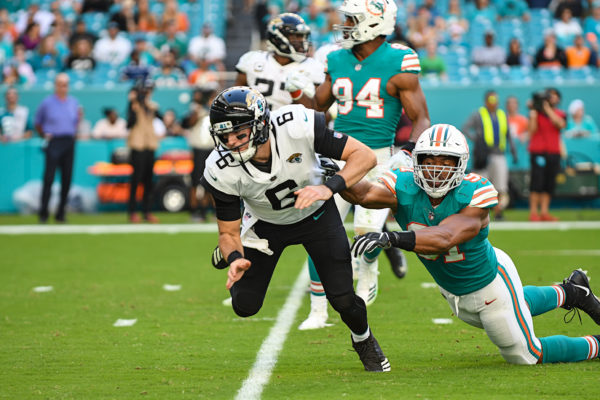 Jacksonville Jaguars quarterback Cody Kessler (6) falls down after contact by Miami Dolphins defensive end Cameron Wake (91)