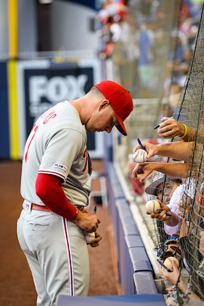 Philadelphia Phillies left fielder Rhys Hoskins (17) signs autographs for fans