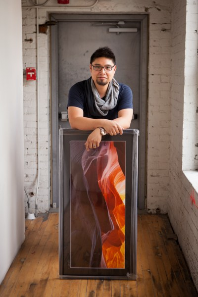 "Fine art photographer and SAIT graduate Jeff Cruz in his downtown studio with one of his framed prints, titled ""Antelope Waves."" Cruz recently celebrated the four-year anniversary of his photography business.— Amanda Siebert, The WEAL"