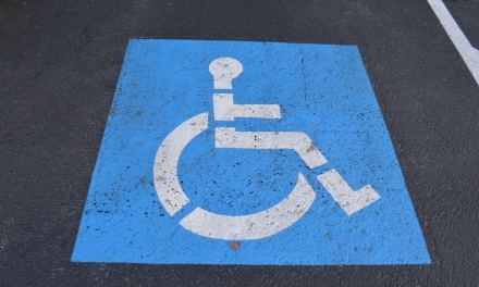 Cet homme attend avec un fauteuil les personnes valides, qui occupent les places des personnes handicapées, pour qu'ils puissent se mettre à leur place jusqu'au bout