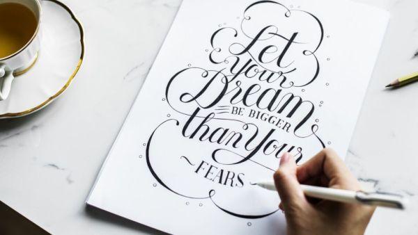 Er wordt een handlettering creatie gemaakt op wit papier