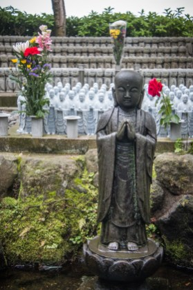 Standing in front of the ranks of small Jizos is Mizukake, or Water-Pouring JIzo. Pouring water over him with a ladle is thought to purify the mind and make wishes come true. Jizo-do, Hase Dera, Kamakura, Japan