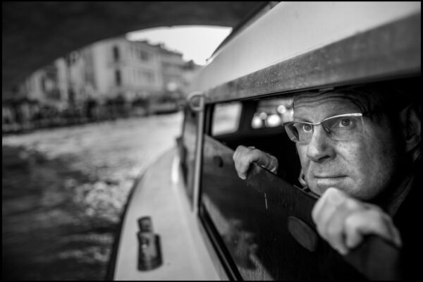 Portrait of Photographer Peter Turnley on a vaporetto boat on his arrival in Venice Italy in October 2019.