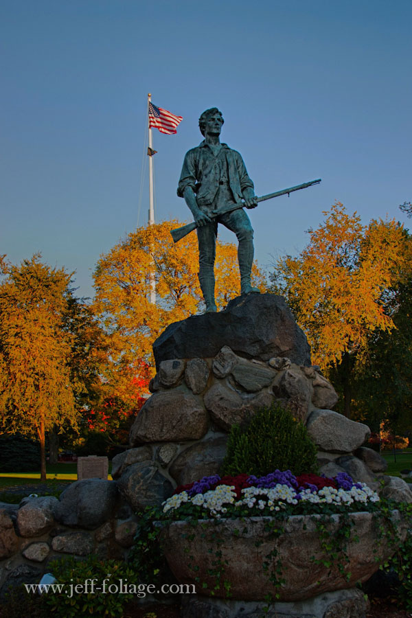 Lexington Minuteman Park and Lexington Mass. with fall colors behind the Minuteman statue