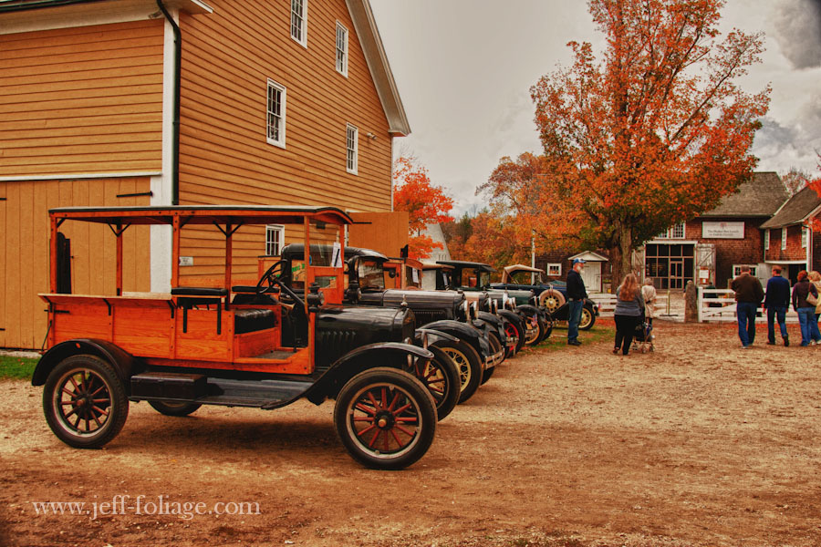 row of antique automobiles next to old building in Canada varies Shaker village New Hampshire