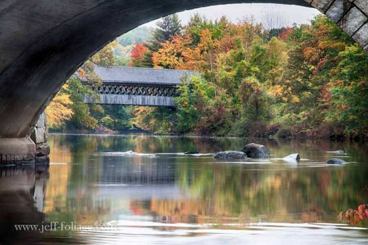 The henniker covered bridge in henniker NH with fall foliage reflecting in the river.