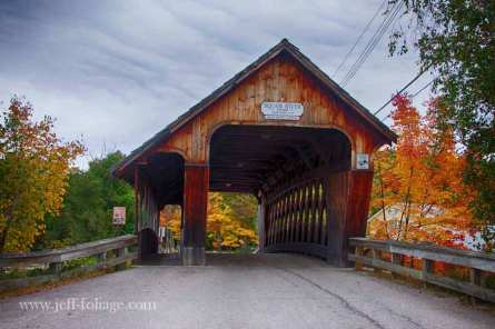 Squam River covered bridge with yellow and orange fall foliage