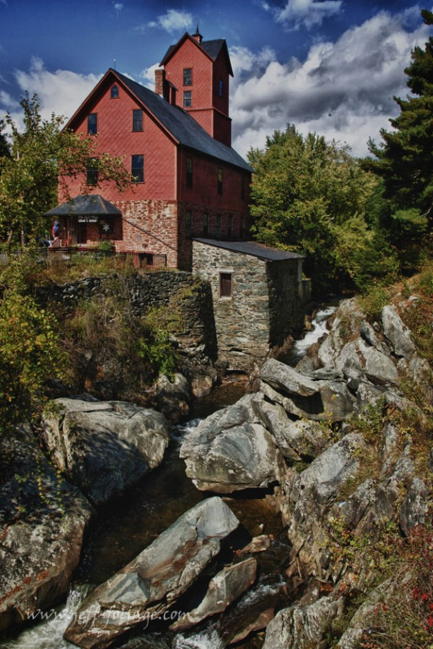A red mill standing over a stream far below