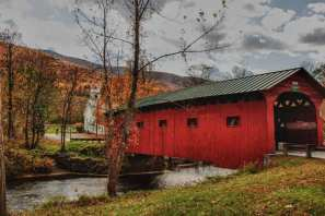 Arlington covered bridge is a red sided bridge that has a green metal roof. There is a great church just past the covered bridge that makes a great visual composition