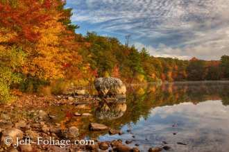 The sun rises and for a moment breaks through the clouds to illuminate the shore and the fall colors of Birch pond in Saugus MA