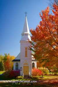 incredible hues of rainbow colors of New England fall colors over a small white church in Sugar Hill New Hampshire.#Vistaphotography #JeffFolger, #JeffFoliage,