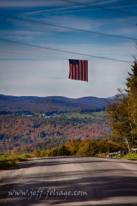As we headed up into the hills above Cabot Vermont the Vermont fall foliage appeared in my side view mirrors along with this flag over Cabot Vermont.