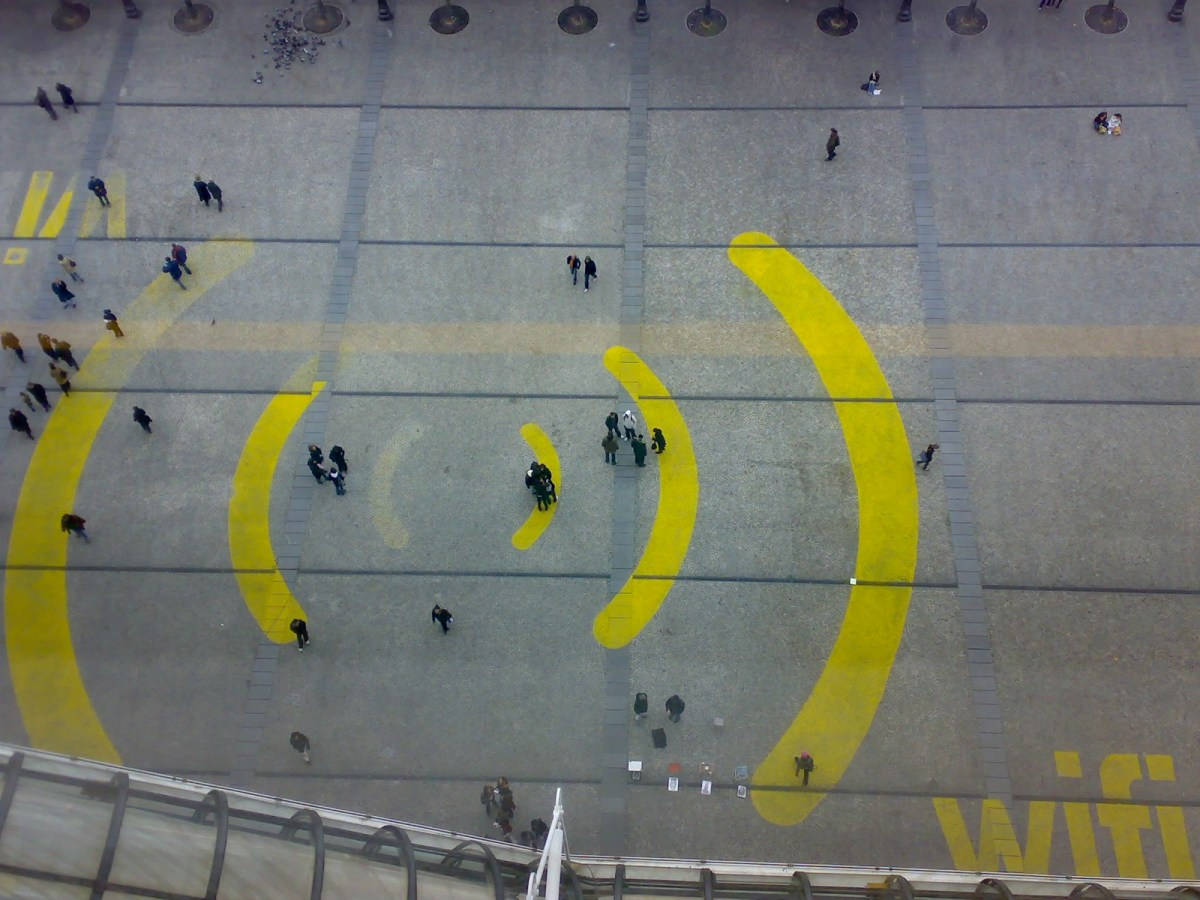 Overhead shot of people walking atop a wifi symbol painted on the ground