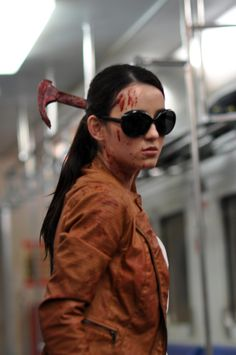 Blood covered Alicia, preparing to fight in a subway and holding a bloody hammer