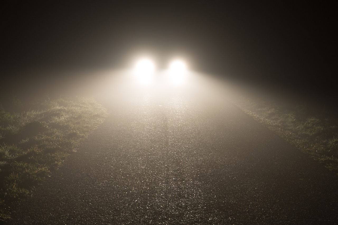 Car headlights cutting through fog