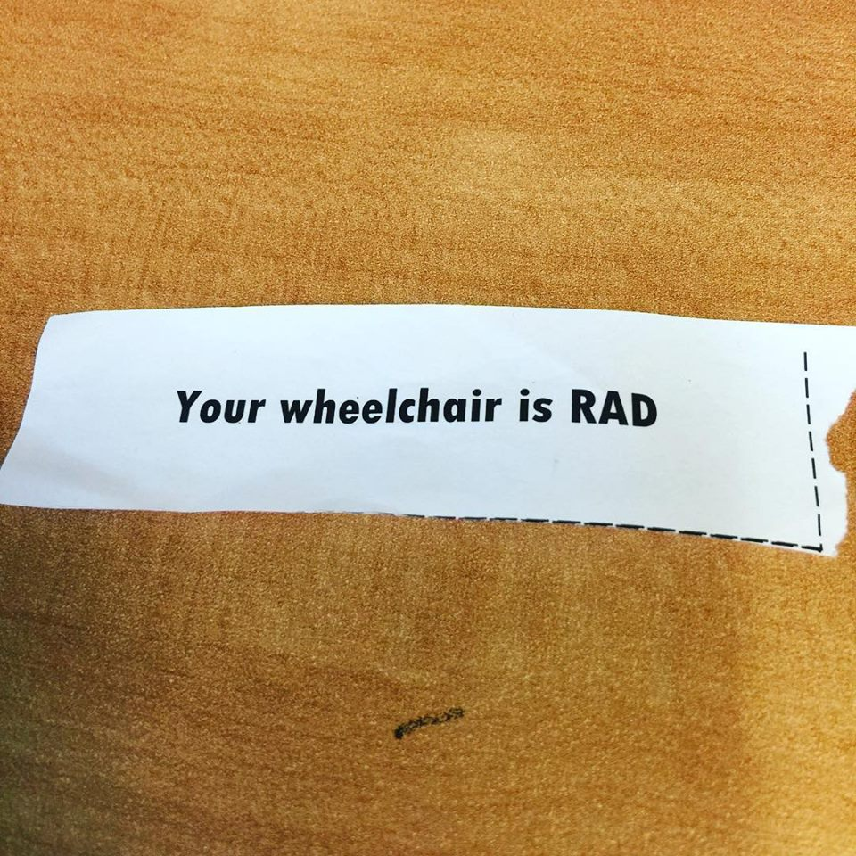 """A white slip of paper with black text that reads """"Your wheelchair is RAD"""""""