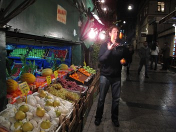 Juggling oranges on a street side fruit stand.