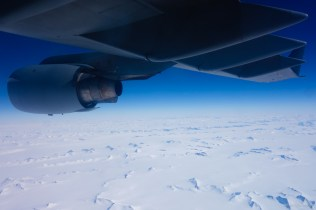 Flying over Antarctica, with the tips of huge mountains poking out from beneath the polar ice cap.