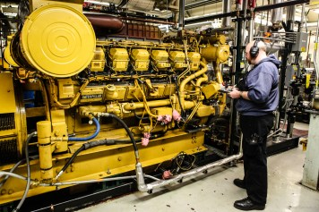 A utility technician taking readings on one of the massive engines which make the station's power and heat. The station burns 600,000 gallons of AN8 jet fuel yearly to keep everything powered up and warm.