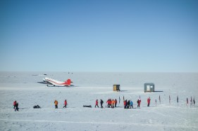 Tourists visiting the south pole. Most tourists arrive on airplanes, such as this DC-3 Basler turboprop. Other groups of tourists ski in, covering the last degree or two degrees of lattitude.