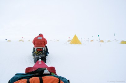 """After a successful landing at field camp and quick briefing in the galley, first order of business was to get our tents and gear setup. In this picture, I'm sitting in our gear sled as we snowmobile to """"Tent City"""", on the edge of camp. Everybody has their own tent, and it's a blend of 4-season mountaineering tents, pointy """"scott tents"""", and dome-shaped """"Arctic Oven"""" tents."""