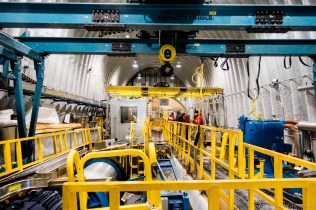 The inside of the main drill arch. Overhead you can see the blue heavy crane. The yellow safety fences are surrounding the Winch Pit, which housed the main winch, level wind, and related machinery. This winch pit leads into the borehole slot, which is about 40 feet deep, 40 feet long, 5 feet wide. Although the borehole is only a few inches in diameter, the slot must be long and wide to accomodate the swing room for the drill tower - it must pivot from vertical to horizontal in one motion.