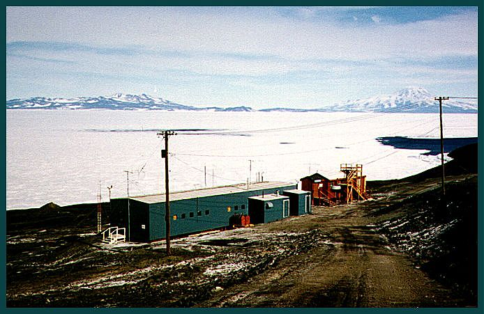 From https://neutronm.bartol.udel.edu/stations/mcmurdo.html : The cosmic ray lab at McMurdo Station, Ross Island, Antarctica. Behind the lab is the Ross Ice Shelf and, on the horizon, Black Island (left) and Mount Discovery (right). Open water at far right leads to McMurdo Sound. Photo by L Shulman, 1991.