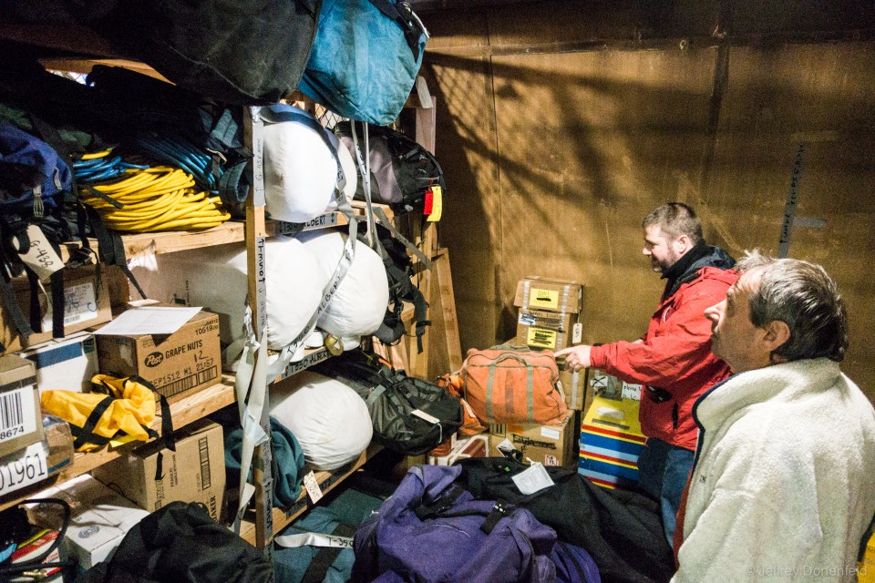 Going through our racks of gear in the cage. You can see sleeping bags, pads, boomerang bags, cots, emergency bags, and all sorts of other supplies.