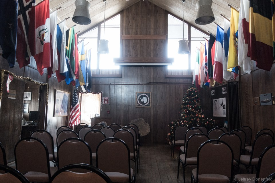 Inside the Chalet, the central space is used as a meeting and presentation hall, with a lectern and projector screen. There's also an upstairs balcony for additional seating.