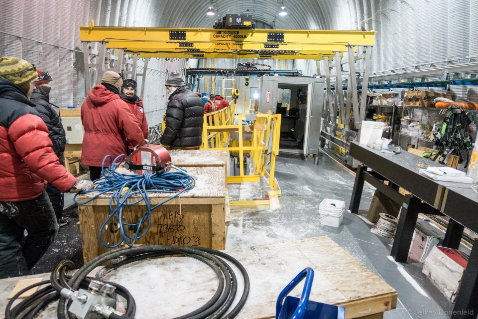 "Looking from the back of the drill arch to the front, the optical table, yellow ""light"" crane, and heated control room are visible. Also notable is the heaving of the floor. As the ice shifts, the floor and overall structure of the arch shifts, buckling everything."