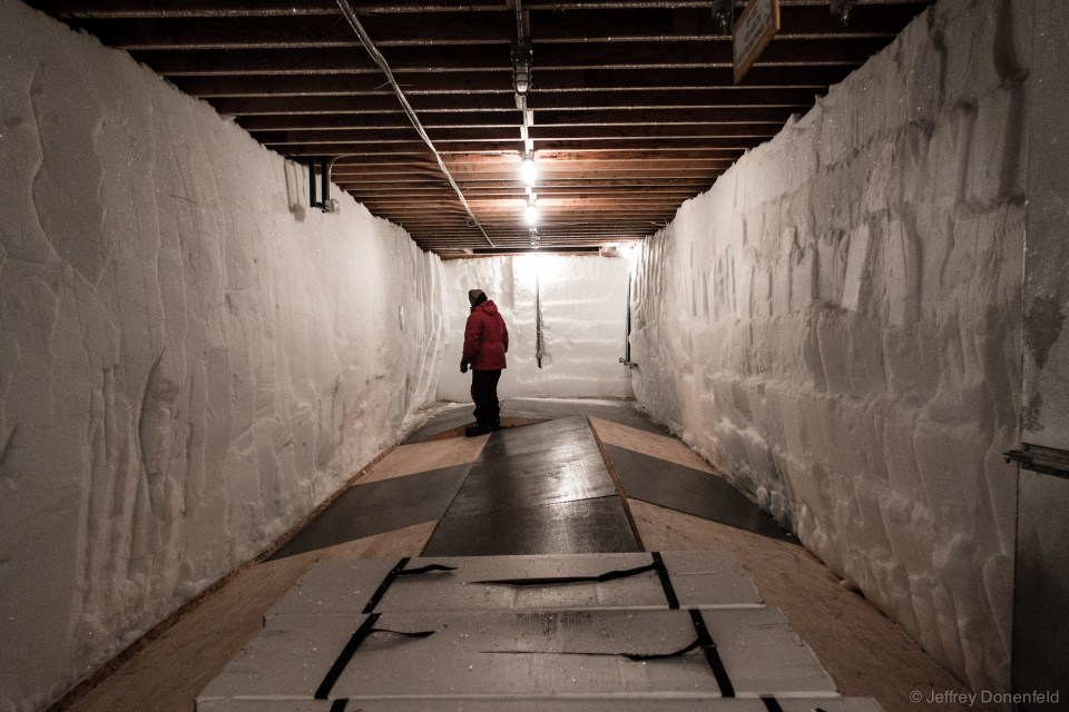 The storage space beneath the ice core processing arch, showing buckled floorboards.