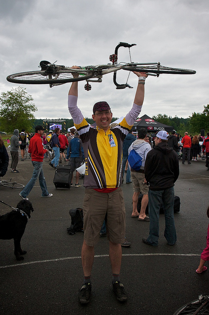 This is a photo of Ross hoisting his bike over his head at the end of the Ride to Conquer Cancer 2011.