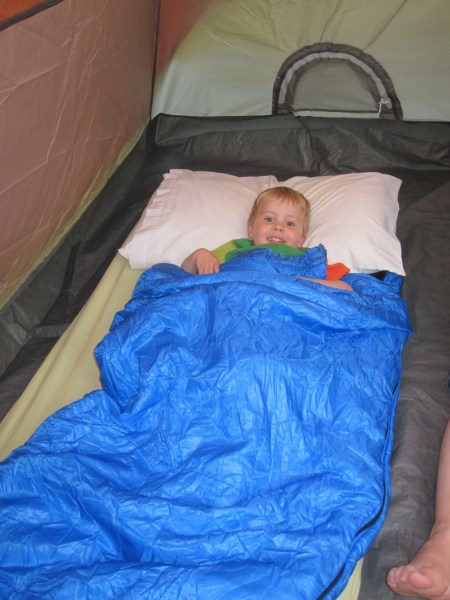 This is a picture of a small blonde 3 year old who is grinning ear to ear in a blue sleeping bag.