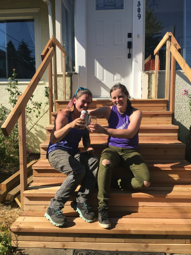 A photo of two smiling female tradespeople sitting on a set of stairs in front of a house toasting the work they have completed.