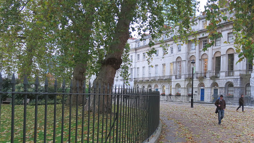 A photo of a corner of Fitzroy Square in London in autumn. Leave s on the ground, plane trees overhead and white Georgian facades