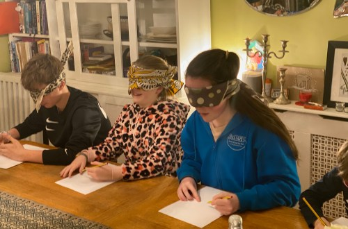Photo of three of my children sitting at the dining table, drawing pictures while blindfolded