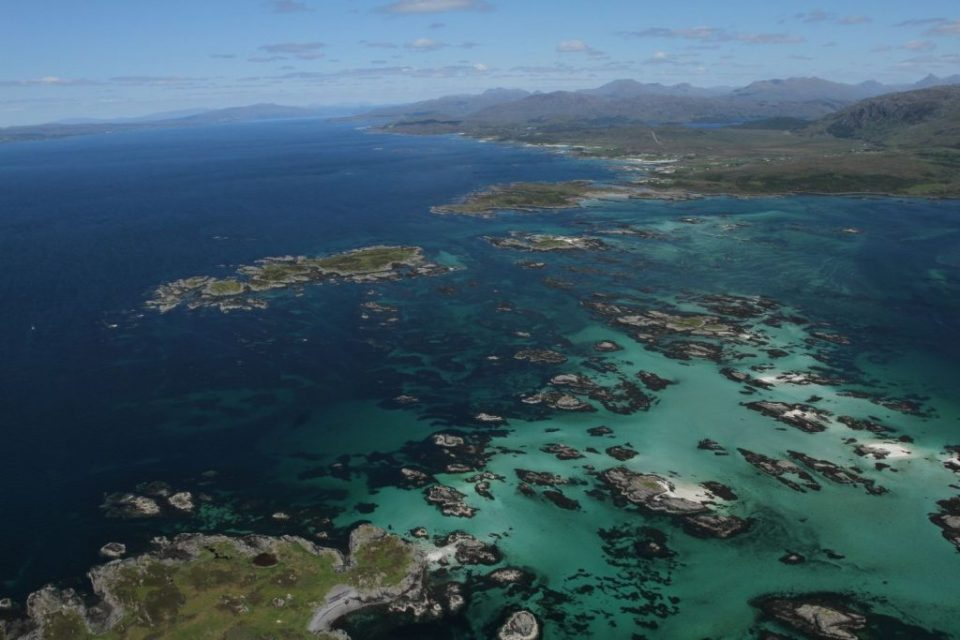Photo of Tiree and Coll, islands in the Inner Hebrides in Scotland, in a deep turquoise sea