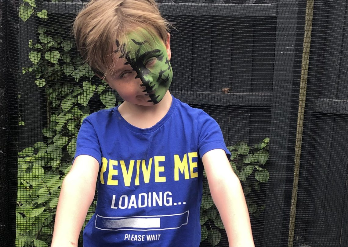 Child with face painted as zombie and t-shirt saying 'revive me'