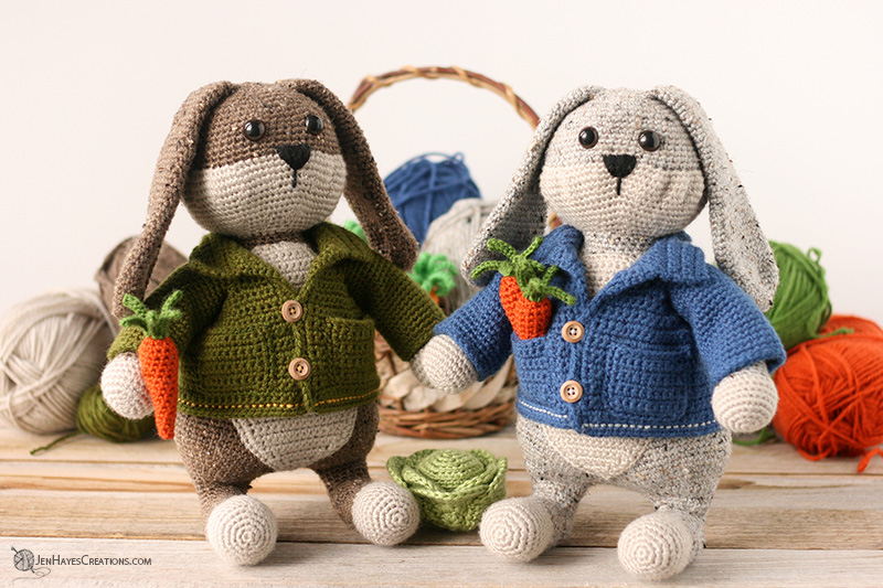 Crocheted brown and cream bunny wearing a green jacket standing by a grey and cream bunny wearing a blue jacket with yarn, a basket, and crochet carrots in the background.