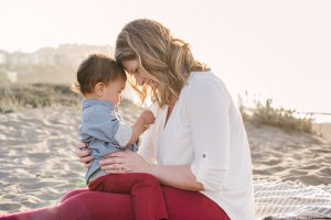 Mother holds her toddler son on her lap on the sand