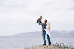 dad holding baby up in air with mom looking