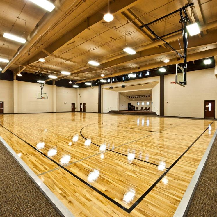 Brightly lit indoor basketball court with shiny hardwood flooring and inset stage.