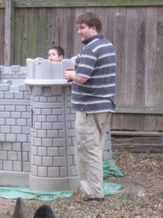 A man with ill fitting polo shirt and baggy cargo pants standing next to a play castle.