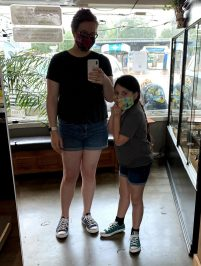 An older woman and younger girl wearing shorts, masked, standing in a piercing shop looking at themselves in the mirror.