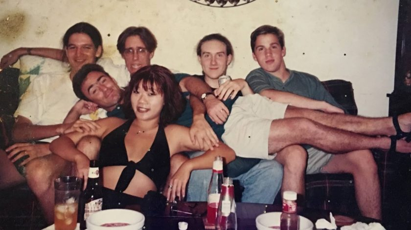 A dirty scanned photo of six people reclining on a couch. Five appear to be boys, with a girl in the front. There are beers on the table in front of them, everyone is smiling.
