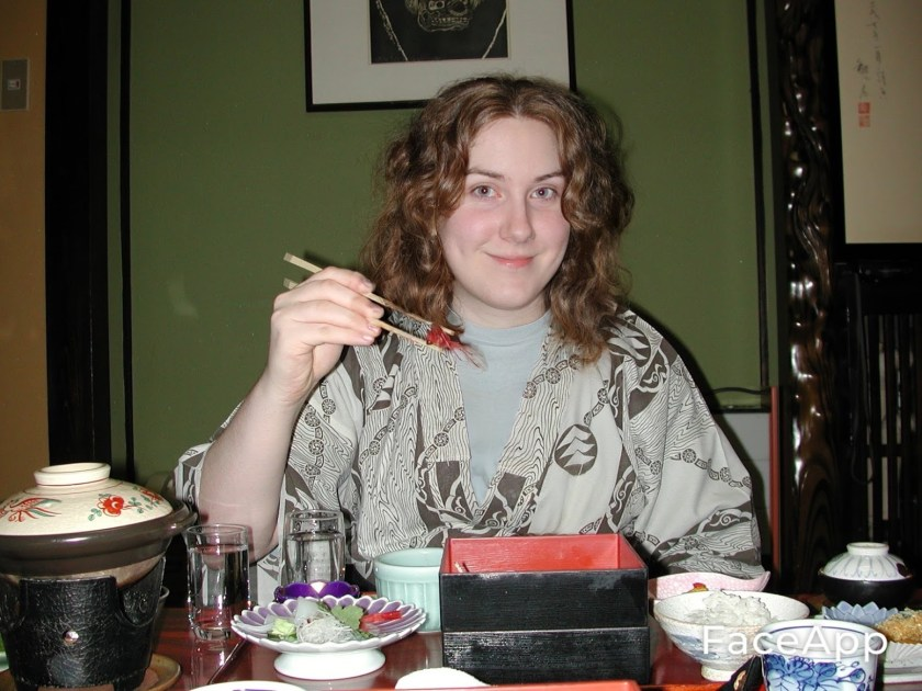 A girl sits behind a low Japanese table wearing a yakuta. She's looking at the camera, holding a shrimp between a pair of chopsticks, smiling. There's a large spread of food on the table in front of her.