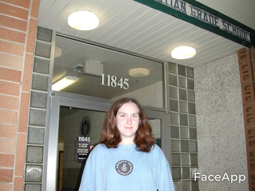 A girl stands, in an extremely oversized blue Amnesty International t-shirt, in front of the front doors of a school.