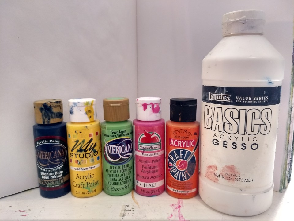 Fluid acrylic craft paints in colors of navy blue, bright yellow, sour apple green, diva pink and orange. White acrylic gesso. Supplies for Art Journaling with Recycled Materials.  art supplies.