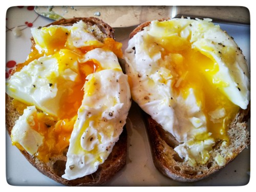 A picture of two poached eggs with the yolks showing. The farm-fresh egg has a a golden-orange yolk, the store-bought egg has a pale yellow yolk.