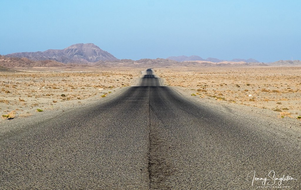 An empty road goes through a desert landscape towards some hills in the distance